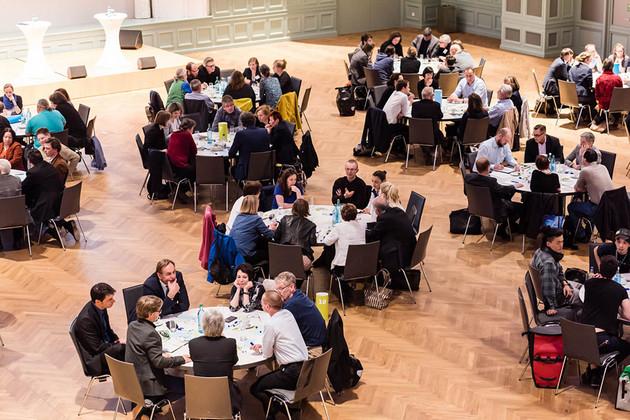 Blick von oben auf sieben runde Tische, an denen diskutiert wird.