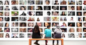 Drei Personen sitzen vor einer Wand, die voll mit Porträtfotos verschiedener Personen ist.