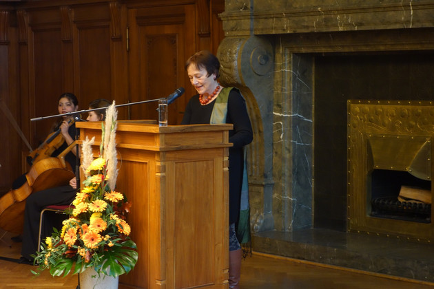 Professorin Dr. Godula Kosack steht hinter einem Stehpult und hält eine Rede. Vor dem Stehpult ist ein hoher Strauß Blumen.