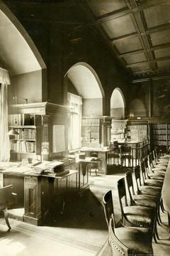 Bild wird vergrößert: Zu sehen ist die Ratsstube im Alten Rathaus Leipzig mit den Arbeitsplätzen für Referendare und Assessoren, die sich auf der linken Bildseite befinden und jeweils im 90-Grad-Winkel zu den Fenstern stehen. Rechts im Bild befindet sich ein langer Tisch mit vielen Stühlen. Das Bild entstand um 1905.