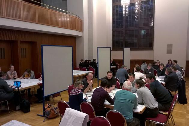 Mehrere Menschengruppen sitzen an verschiedenen Tischen in einem großen Saal und diskutieren.