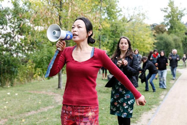 Frau Wu spricht in ein Megaphone, hinter ihr laufen Menschen (Teilnehmer am Stadtrundgang)