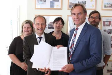 Bild wird vergrößert: OBM Jung, Minister Ulbig und Akteure des Leipziger Westen zeigen den Förderbescheid.