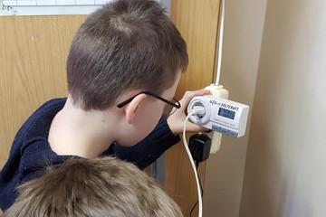 Bild wird vergrößert: Ein Junge - von hinten fotografiert - liest von einem Stromverbrauchsmessgerät ab.