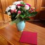 Ein Blumenstrauß auf einem Tisch, danebe liegt eine Urkunde mit roten Umschlag