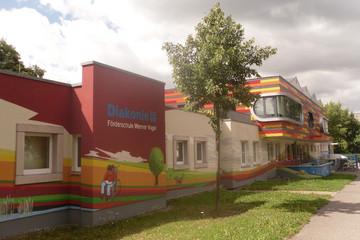 Bild wird vergrößert: Ein bunt bemaltes Gebäude mit verschiedenen Zeichnungen, unter anderem mit einem Baum, einem Hund und einem Kind im Rollstuhl, das liest.