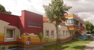 Ein bunt bemaltes Gebäude mit verschiedenen Zeichnungen, unter anderem mit einem Baum, einem Hund und einem Kind im Rollstuhl, das liest.