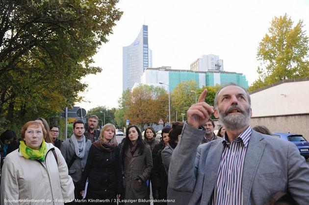 Eine Gruppe von Menschen inmitten der Stadt. Alle schauen leicht nach oben. Ganz vorne steht ein Herr mit Vollbart. Er zeigt mit dem Finger himmelwärts.