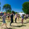 Veranstaltungsgelände im Panorama, in der Mitte mehrere Menschen, die Zumba tanzen, ringsherum Pavillion mit Girlanden und bunten Luftballons