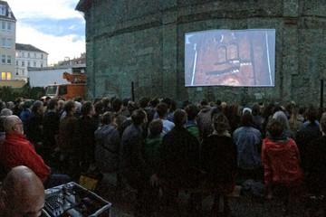 Bild wird vergrößert: Auf der Außenmauer des ehemaligen Kinos ist eine Leinwand montiert. In der Dämmerung stehen viele Zuschauer davor und schauen einen Film.