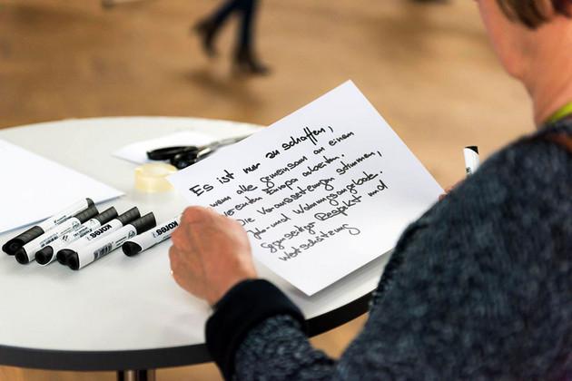 Eine Frau hat einen beschriebenen Zettel in der Hand und schaut drauf.