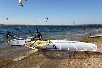 Bild wird vergrößert: Windsurfer am Strand eines Sees. Im Hintergrund sind viel Segel von Kitesurfern zu sehen.