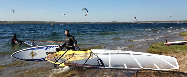 Windsurfer am Strand eines Sees. Im Hintergrund sind viel Segel von Kitesurfern zu sehen.