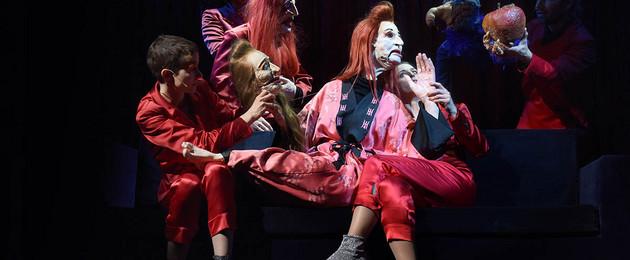 Mehrere Schauspieler mit Masken und Puppen auf einer dunklen Bühne.