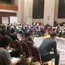 Ein Saal voller Menschen auf Stühlen, die auf großen einen Stadtplan am Boden schauen.