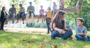 Personen mit unterschiedlicher Herkunft sitzen auf einem Baumstamm und einer Wiese