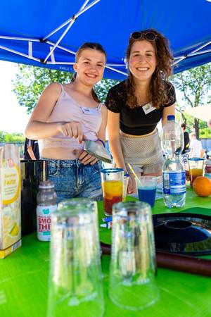 Zwei junge Frauen lächeln in die Kamera. Eine hält eine silberne kleine Schaufel. Vor ihnen steht ein Cocktail.