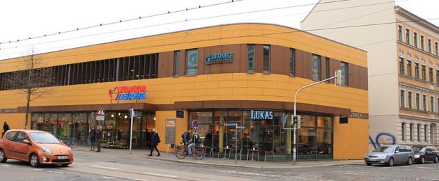Das Foto zeigt ein multifunktionales Gebäude. Im Erdgeschoss befindet sich ein Konsum. In der Etage darüber befinden sich Praxen, ein Sportstudio und Parkflächen.