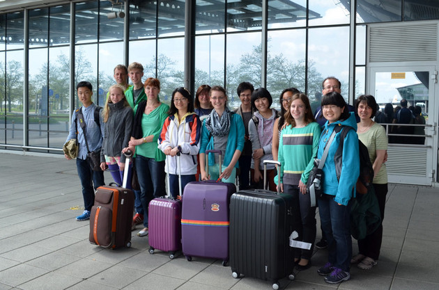 Gruppenfoto vorm gläsernen Eingang zum Flughafen mit Schülern und Koffern