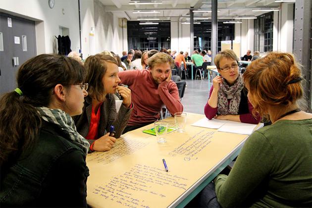 Teilnehmende des Themenabends diskutieren am Tisch.