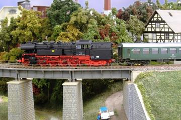 Bild wird vergrößert: Modeleisebahnlok fährt über Miniaturbrücke
