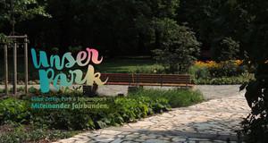 """Gepflasterter Weg im Staudengarten des Clara-Zetkin-Park. Auf dem Bild ist das Logo """"Unser Park"""" eingebunden."""