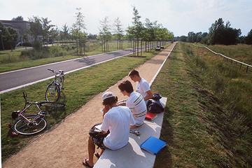 Bild wird vergrößert: Jungendliche auf eine Steinbank am Fahrradweg im Grünen Bogen Paunsdorf