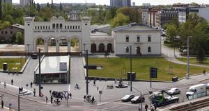 Bild vom Bayerischen Bahnhof mit Vorplatz und historischem Portikus und Straßenverkehr davor.