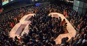Menschenmenge steht um eine 89, die aus Kerzen geformt ist.