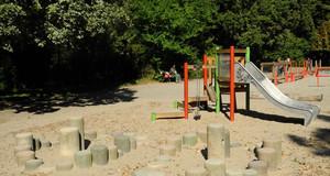 Sandspielfläche mit kleiner Kletter-Rutsch-Kombination und Klettersteinen.