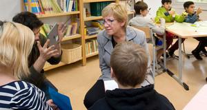 Kinder sitzen in einem Schulraum und erzählen einer Frau etwas