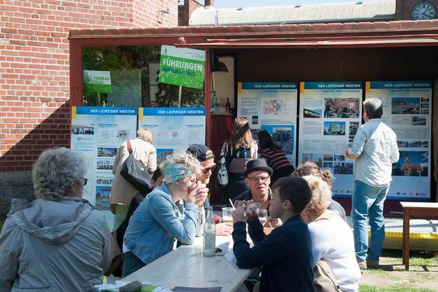 Mehrere Personen sitzen an einem Tisch im Freien und essen. Im Hintergrund schauen sich Leute große Infotafeln an.