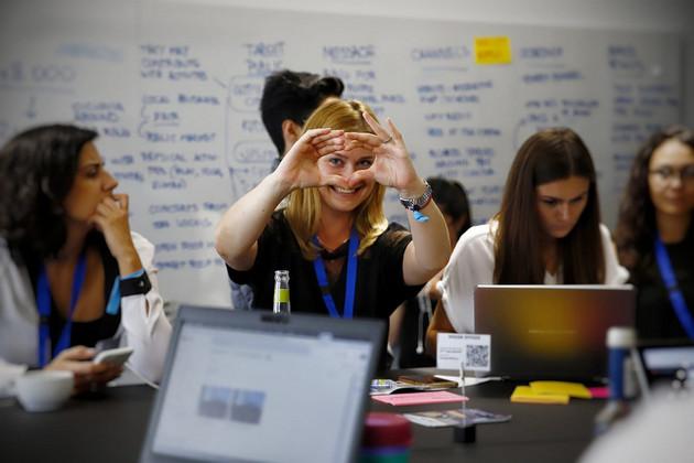 Workshopteilnehmer arbeiten mit Laptops an einem Tisch. Eine Frau formt mir ihren Händen ein Herz.