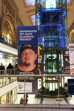 """Bild wird vergrößert: Großes Banner auf dem Hauptbahnhof mit dem Statement """"Demokratie ist auch Glaubensfreiheit"""" und dem Gesicht eines Mannes"""