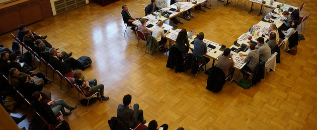 Die Mitglieder des Jugendparlaments sitzen an zu einem großen Rechteck gestellten Tischen. Weitere Zuschauer sitzen daneben.