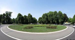 Im Vordergrund die Straße des Kreisverkehrs, dahinter eine Grünfläche mit kleineren Hecken in Dreiecksform, in der Mitte ein rundes Beet