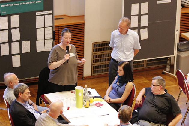 Gruppe von Menschen an einem Tisch. Frau Gabelmann steht am Tischende und redet in ein Mikrofon.