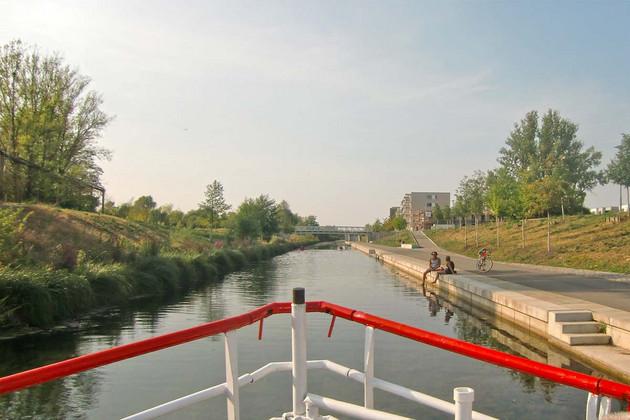 Die neuen Wohnhäuser des Lindenauer Hafens vom Wasser aus gesehen, auf der Hafenmauer sitzen Menschen, ein Ruderboot ist etwas weiter entfernt.