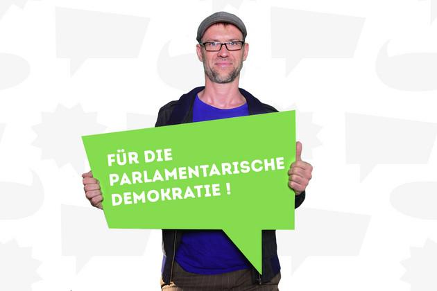 """Ein Mann hat sich mit dem Statement """"Für die parlamentarische Demokratie!"""" auf einer grünen Sprechblase fotografieren lassen."""