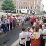 Viele Menschen stehen auf der Straße und hören einem Kinderchor  zu. Die Kinder tragen traditionelle ukrainische Kleidung, die Mädchen im Chor bunte Blumenkränze auf dem Kopf und Schleifen im Haar.