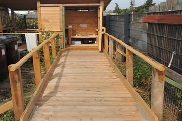 Bild wird vergrößert: Eine Holzrampe führt zu einer behindertengerechten Toilette.