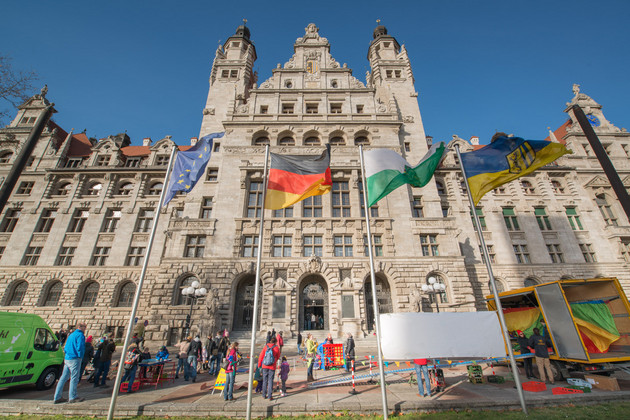 Das Bild zeigt die Vorderansicht des Neuen Rathauses mit Besuchern und zwei Spielmobilen im Aufbau.