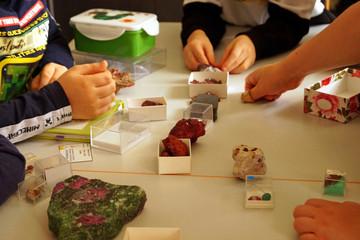 Bild wird vergrößert: Auf einem Tisch liegen verschiedene Mineralien, Kinderhände greifen danach.