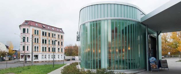 Glasfassade eines neuen Baus für ein Einkaufszentrum und altes Wohngebaüde aus der Gründerzeit