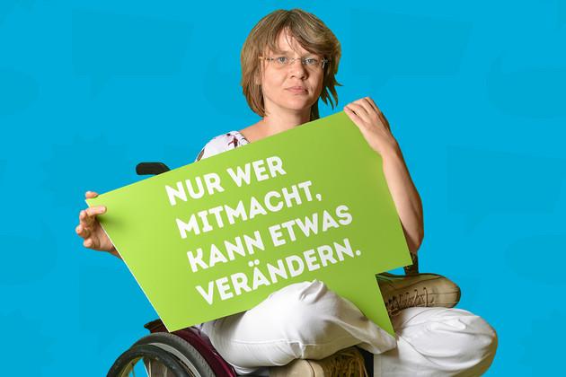 """Frau im Rollstuhk zur Statementkampagne zum Jahr der Demokratie mit grüner Sprechblase auf der steht """"Nur wer mitmacht, kann etwas verändern."""""""