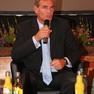 Der Oberbürgermeister im Anzug mit hellblauer Krawatte, dabei ein Mikrofon haltend, spricht während einer Podiumsdiskussion