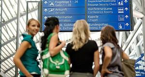 Menschen vor Hinweisschildern im Flughafen Leipzig-Halle