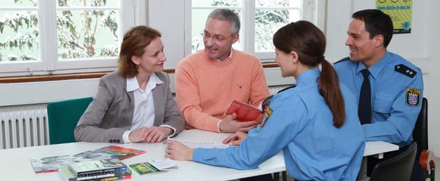 Ein Mann und eine Frau sitzen am Tisch und lassen sich von zwei Polizisten beraten.