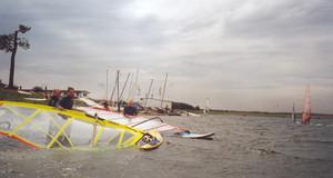 Windsurfer tragen ihr Surfbrett in den Cospudener See