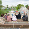 Eine Menschengruppe sitzt auf Sitzmöglichkeiten auf dem Gelände des ehemaligen Plagwitzer Güterbahnhofes. Vor der Gruppe steht ein Mann und redet.